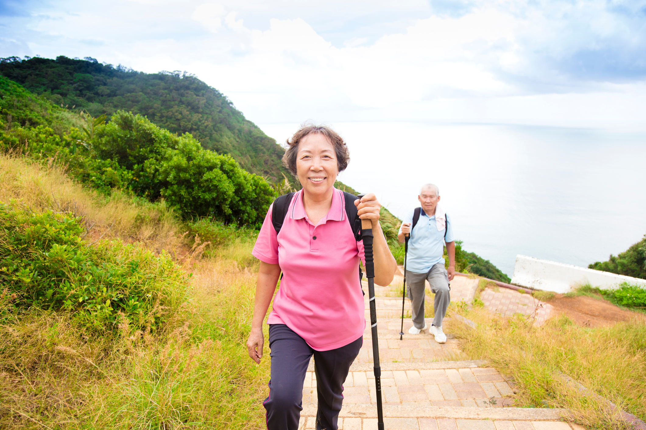 Older couple hiking with poles